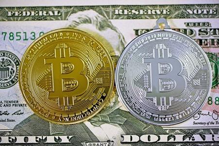 Bitcoins on top of a dollar